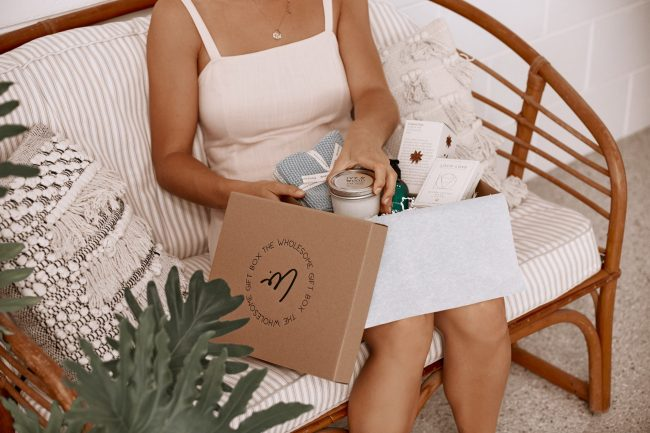 lady sitting on couch opening personalised gift box from the wholesome gift box